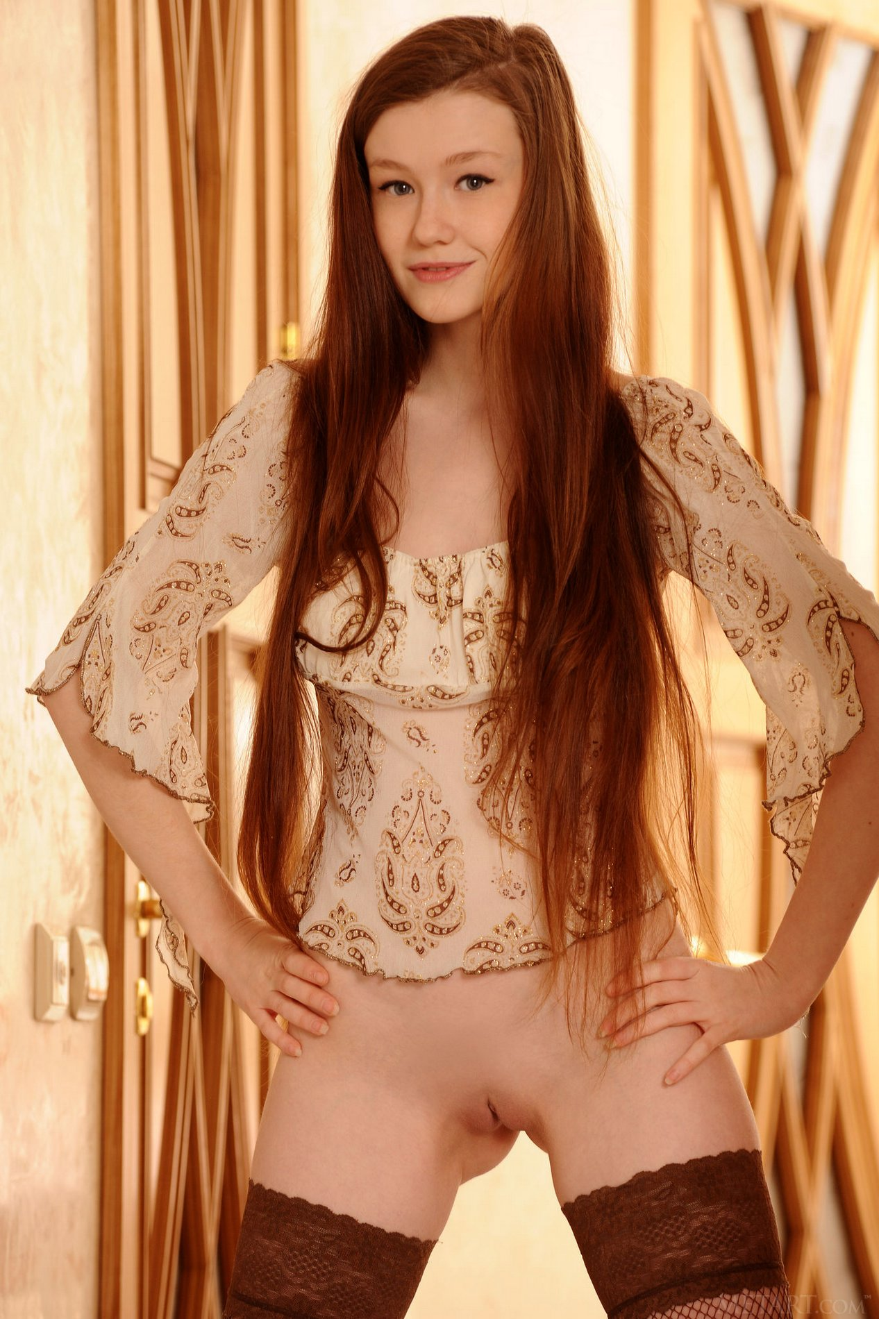 Cute redhead Emily Bloom in sexy stockings poses for camera.