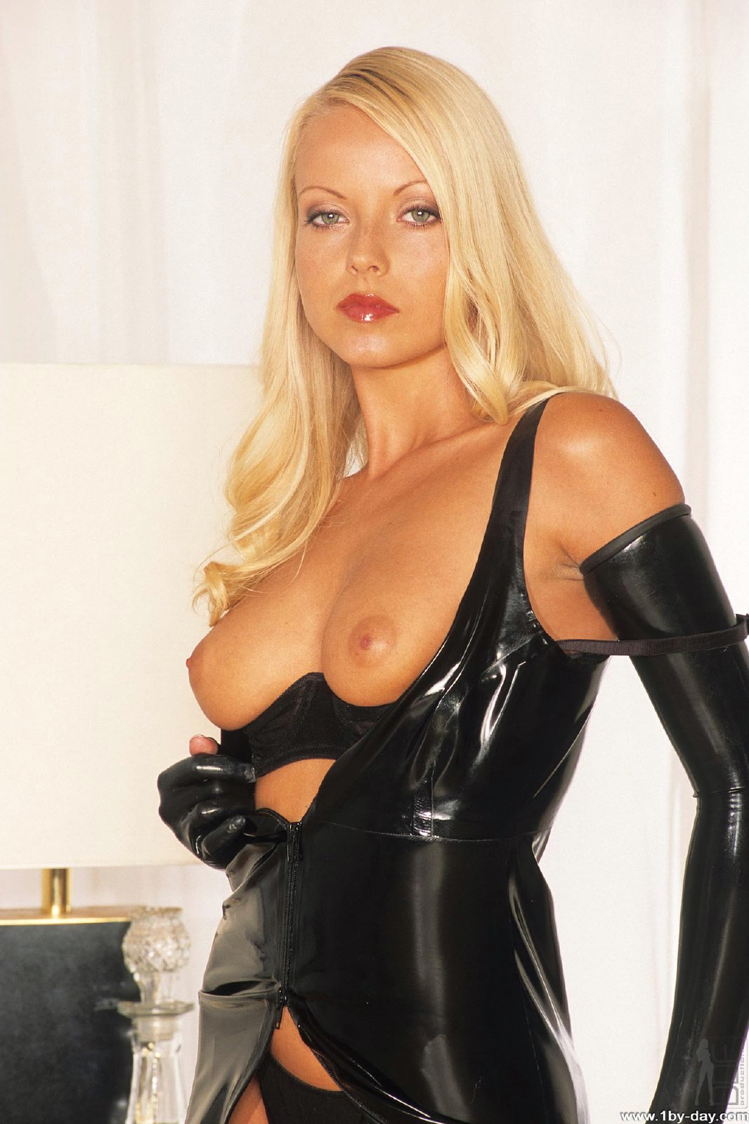 Mistress Jana Cova in latex outfit posing in front of the ...