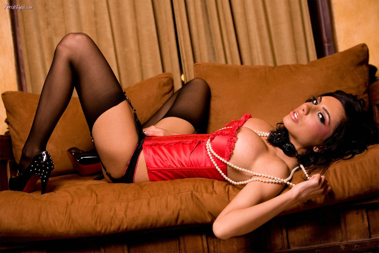 lela star in red corset and black stockings posing on sofa