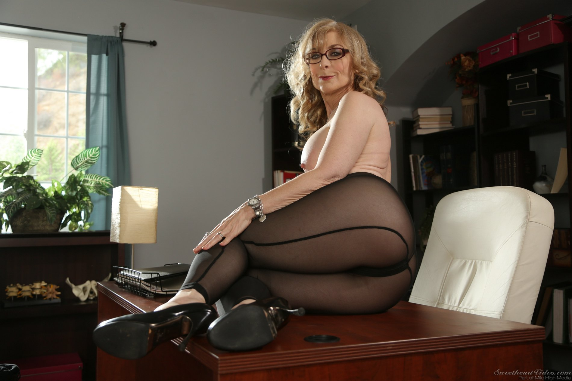 Nina Hartley in black pantyhose and heels posing in the office.