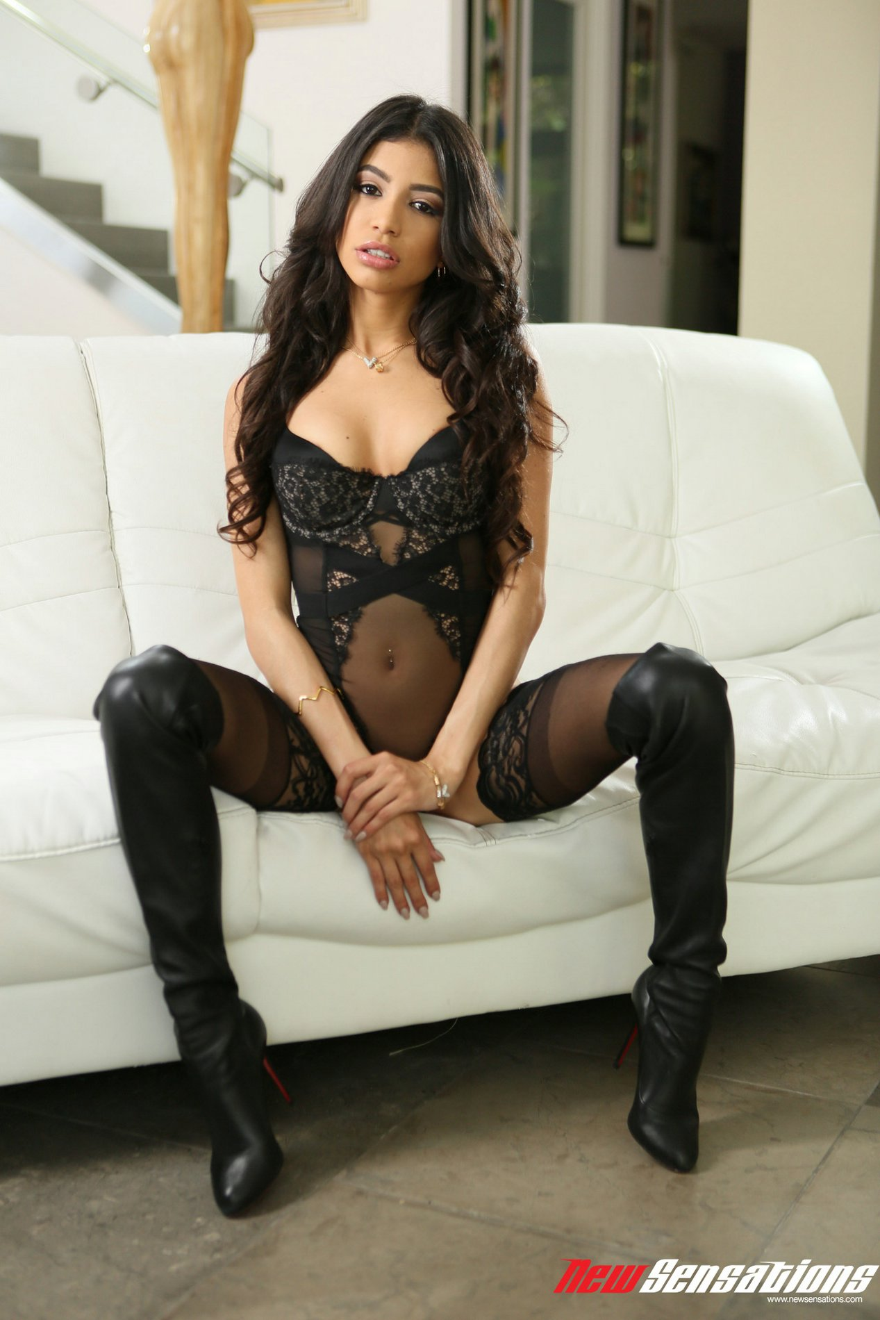 Veronica Rodriguez in black stockings and high boots poses for camera.